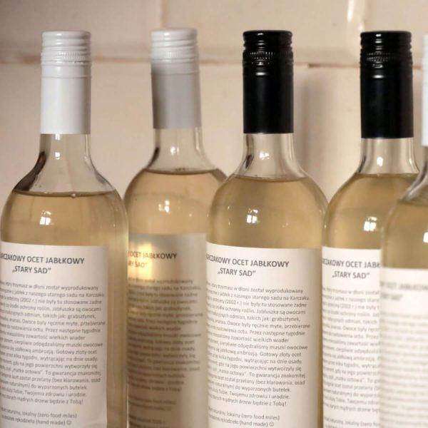 Szklane butelki z płynem koloru żółto-słomkowego, zakrętkami metalowymi w kolorze białym i czarnym i białymi etykietami na tle kaflowego pieca
